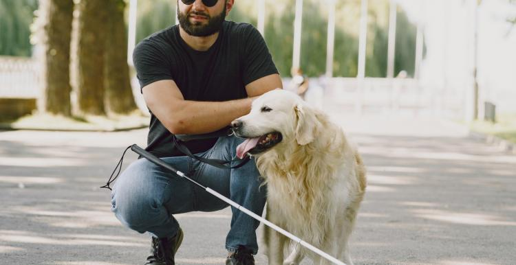 Photo of blind man with guide dog
