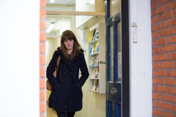 Woman alone walking out of the door looking down