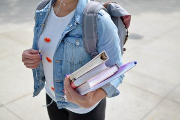 Photo of student holding books (by Unsplash)